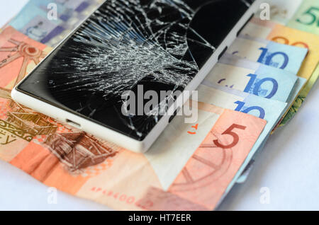 Broken smartphone lying on money banknotes on a White background. Losing money concept - Stock Photo