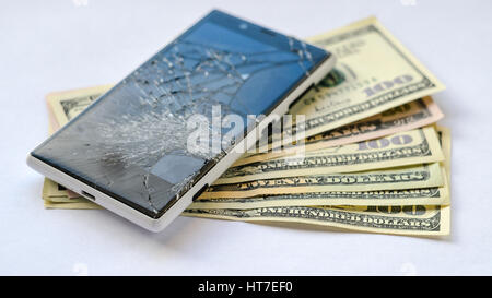 Smartphone with broken display lying on money banknotes on white background. Need new smartphone concept - Stock Photo