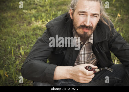 Young asian bearded man smoking pipe in summer park, closeup portrait - Stock Photo