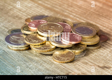 Euro coins piled on wooden table. Financial concept. - Stock Photo
