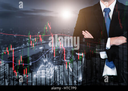 Double exposure of Businessman and trading stock market graph and bar on city at night. Business financial and trading - Stock Photo