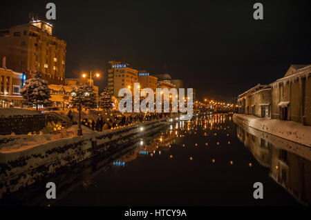 Lanterns on the banks and across the canal light up the cold Otaru evening for the Snow Gleaming Festival - Stock Photo