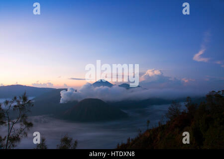 White smoke coming out of volcanoes surrounded by white clouds of mist and a clear blue sky seen at a distance in - Stock Photo