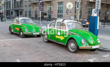 Two green antique car standing on the street - Stock Photo