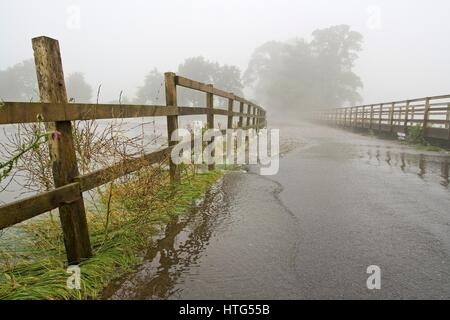 A view down a flooded road leading on a misty day with trees faintly showing in the background. - Stock Photo