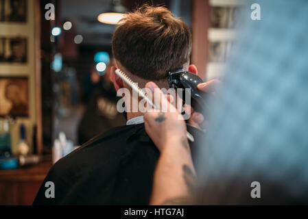 Barber hands makes hairstyle of the client man by clipper. Male person sitting at the mirror in barbershop - Stock Photo