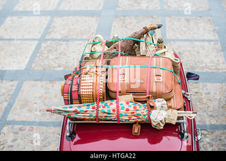 Spanish holidays in 50's style in a small car all packed on a roor top - Stock Photo