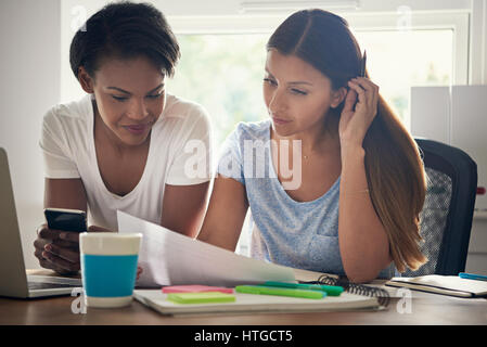 Two successful female entrepreneurs working together in the office discussing a spreadsheet with statistics at a - Stock Photo