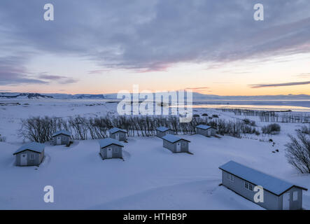 Early dawn sunrise in winter in Iceland, with bungalow chalets in foreground - Stock Photo