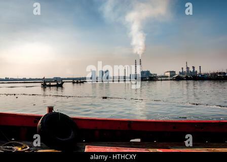 Emitting smokestacks of the Muara Karang steam-powered power plant seen from the Muara Karang fishing harbor, Jakarta. - Stock Photo
