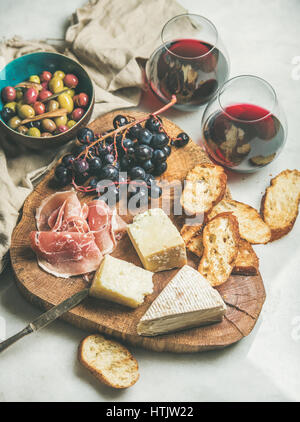 Cheese, olives, prosciutto, baguette slices, grapes and red wine - Stock Photo