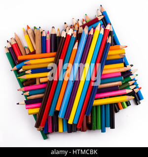 Top view of many colored pencils arranged in a pile on top of each other isolated on white background - Stock Photo