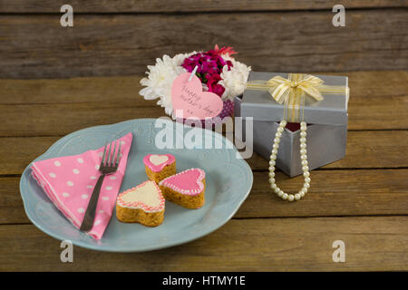 Open gift box with flower vase and heart shape cookies on wooden plank - Stock Photo