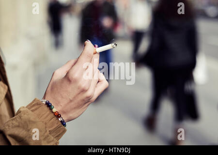 closeup of a young caucasian woman with purple nail polish in her fingernails smoking a cigarette in the street - Stock Photo