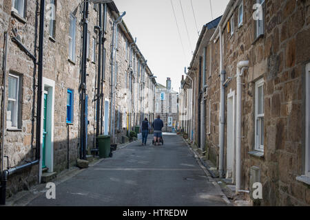 A man and women walk down a street past terraced houses in the town of St Ives, Cornwall, UK. - Stock Photo