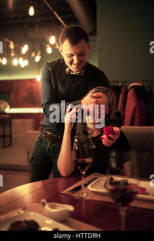 Young man makes woman marriage proposal, he closed her eyes with his hand and holds in front of her jewelry case - Stock Photo
