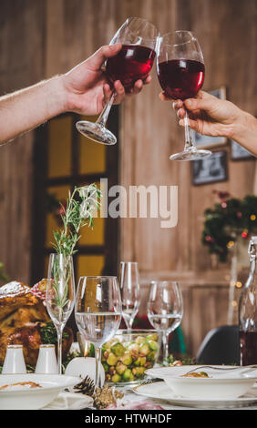 Partial view of couple toasting glasses of red wine at Christmas dinner - Stock Photo