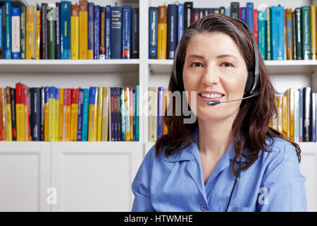 Friendly middle aged woman with headset and a blue shirt in front of lots of books, talking to a customer via the - Stock Photo