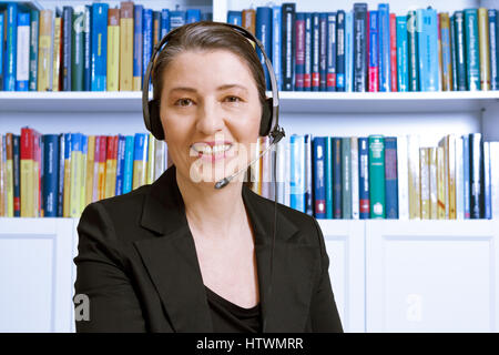 Friendly smiling middle aged woman with headset and black blazer in an office with lots of books, lawyer or accountant, - Stock Photo