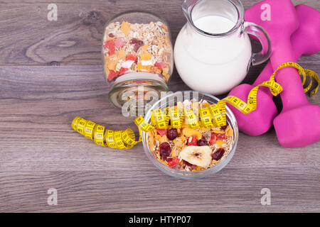 Fitness concept with weights, yoghurt, muesli and fruit on a wooden background - Stock Photo