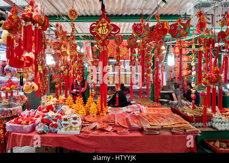 Chinese new year decorations hanging up for sale at a market in Hong Kong. - Stock Photo
