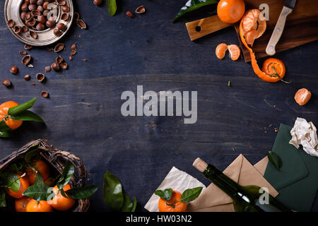 Mandarin fruits with hazelnuts and wine on wooden background. Healthy organic food frame. Top view, copy space, - Stock Photo