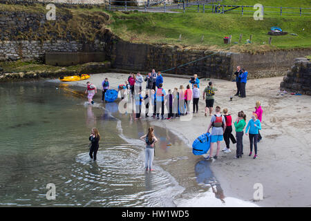 youth group takes advantage of a fine spring afternoon for water sports in the small harbor at Ballintoy on the - Stock Photo