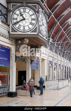 Travellers at Paddington Mainline Station, London, UK. Family sayng hello to Paddington Bear statue. March 2017. - Stock Photo