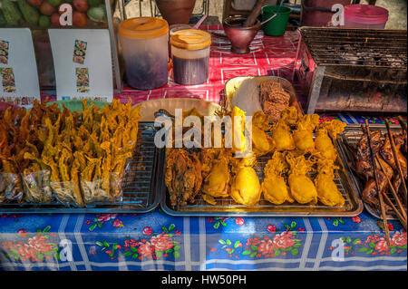 Thailand, Krabi Province. Thai fast food - fried in batter in boiling oil seafood, chicken wings, fried on coals. - Stock Photo