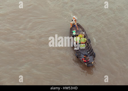 Can Tho, Vietnam - APRIL 2: Woman and boy on boat floating down Mekong river at Can Tho Floating Market, Can Tho, - Stock Photo