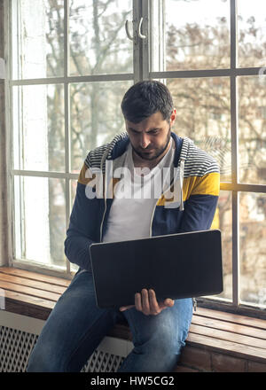 Hipster bearded man using laptop or notebook while sitting on the windowsill. Big windows on background. - Stock Photo