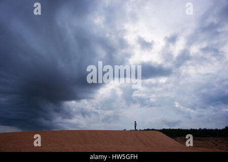 Silhouette of man standing on a desert sand dune facing dark black storm cloud in the evening, Vietnam. - Stock Photo