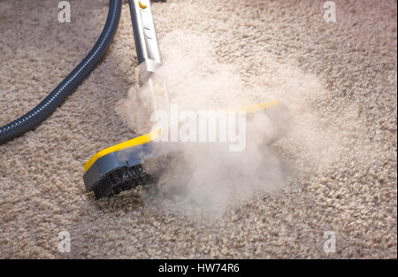 Using dry steam cleaner to sanitize floor carpet. - Stock Photo