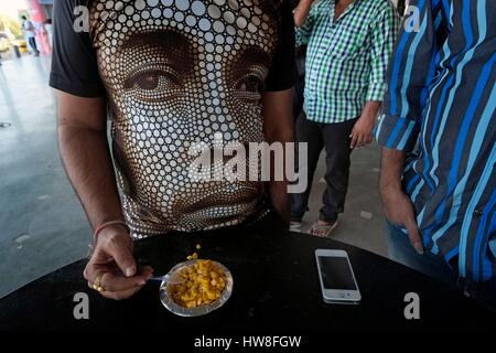 India, Gujarat State, Bhuj, men wearing shirts and a t-shirt representing a man's face at a bus parking area - Stock Photo