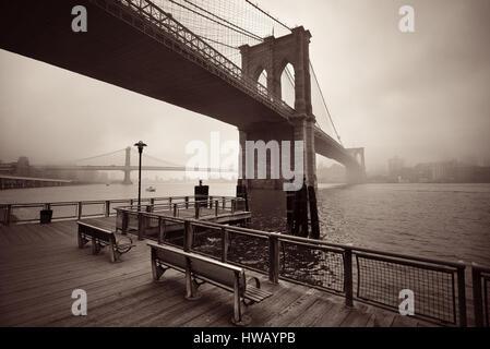 Brooklyn Bridge in a foggy day in downtown Manhattan - Stock Photo