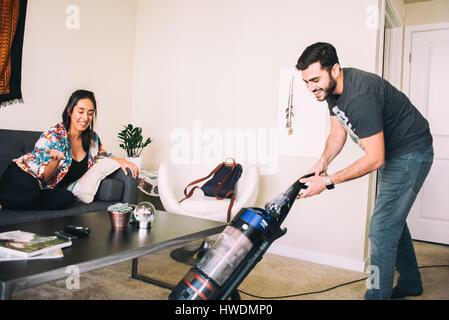 Woman supervising man vacuuming carpet - Stock Photo