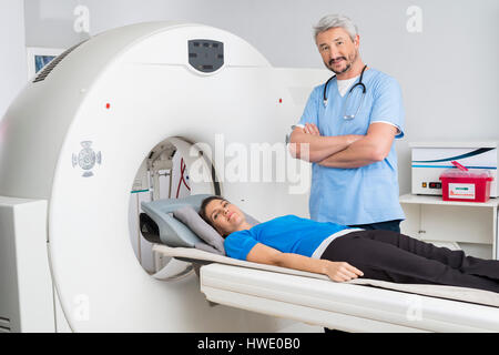 Doctor Standing Arms Crossed By Patient Lying On MRI Machine - Stock Photo