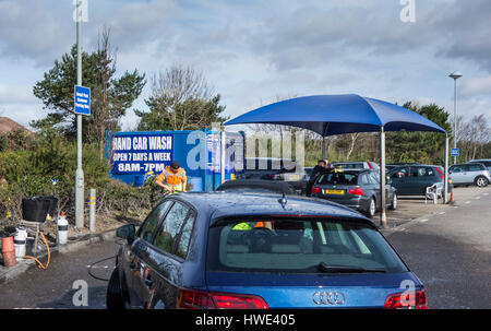 Cars Being cleaned at a Hand Car Wash  Unit in a Car Park in Poole, Dorset, UK - Stock Photo