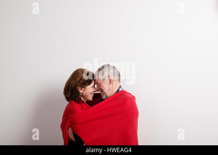 Senior couple hugging, wrapped in red blanket. Studio shot. - Stock Photo