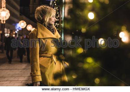 Mature woman christmas window shopping at night, Munich, Germany - Stock Photo