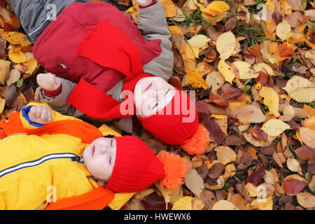 kids in autumn laying in leaves  - Stock Photo