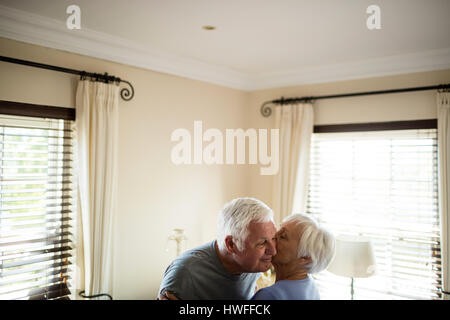 Senior couple embracing each other in bedroom at home - Stock Photo
