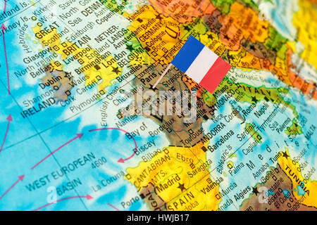 map with miniature flag of France .Selective focus on French Flag. Backlit lighting - Stock Photo