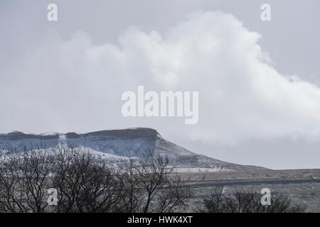 Addlebrough in spring with snow laden cumulus clouds, seen from Mill Gill, Askrigg, Wensleydale, Yorkshire Dales - Stock Photo
