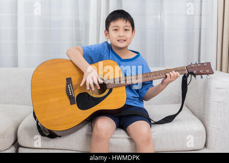 Happy Asian Chinese little boy playing guitar on the sofa in the living room at home. - Stock Photo