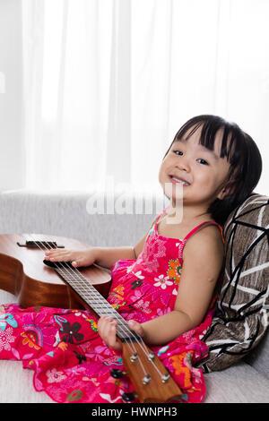 Happy Asian Chinese little girl sitting on the sofa playing ukele - Stock Photo
