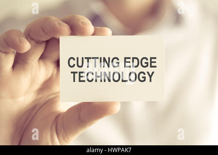 Closeup on businessman holding a card with text CUTTING EDGE TECHNOLOGY, business concept image with soft focus - Stock Photo