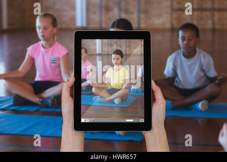 Close-up of hands holding digital tablet against school kids meditating during yoga class - Stock Photo