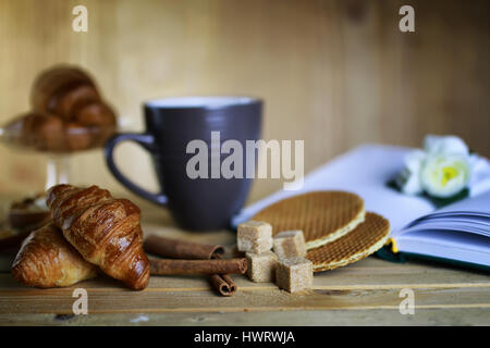 cup with tea croissant book - Stock Photo