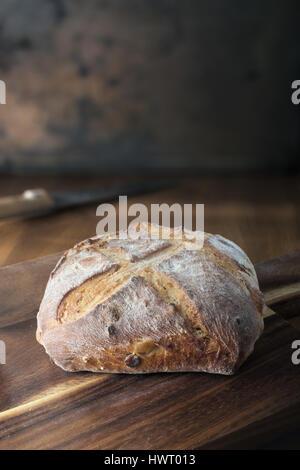 Rustic bread on cutting board - Stock Photo